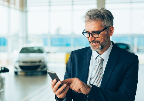 Man Smiling at Phone While Using Our Dealership Social Media Marketing for Naperville IL